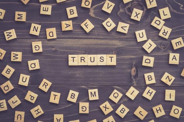 ビジネスコンセプトのテーブルに信じる単語の木ブロックを信じてください。