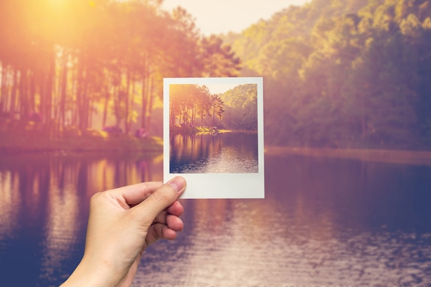 手を保持するインスタント写真ヴィンテージ効果と池の水と日の出。