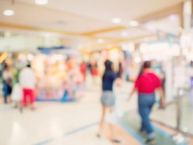 ぼやけた背景画像。ショッピングモールの人々はボケとヴィンテージトーンで背景をぼかします。