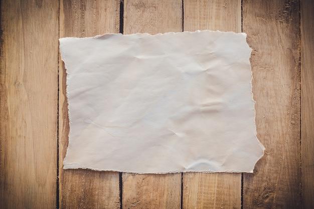木製の背景に裂かれた古い紙