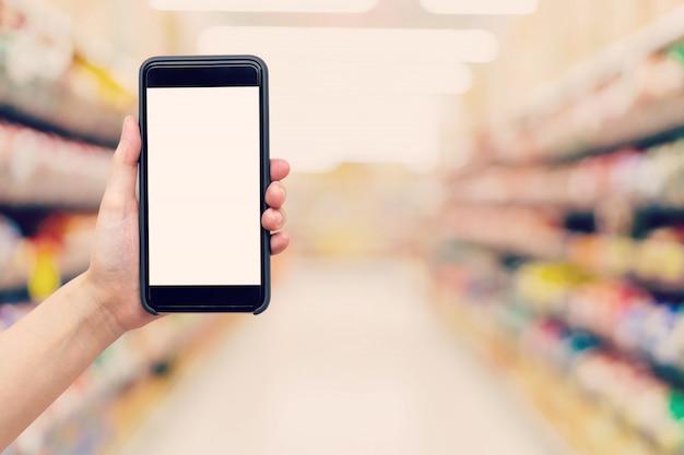 手を握って、ショッピングモールでぼんやりした背景と電話を表示する女性。