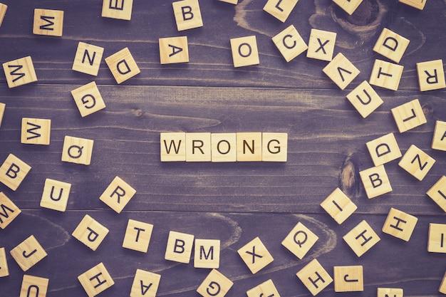 ビジネスコンセプトのテーブルに間違った単語の木ブロック。