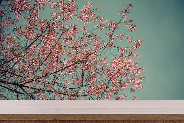 製品またはモンタージュのための空の木製テーブルとヴィンテージ調のピンクの花。