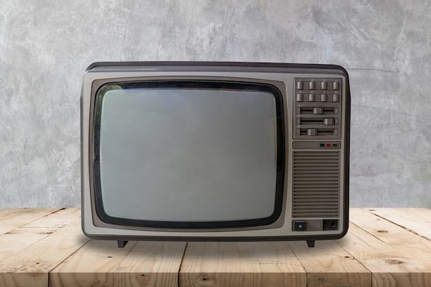 木製のテーブルとセメントの壁のテクスチャと背景にヴィンテージのテレビ。