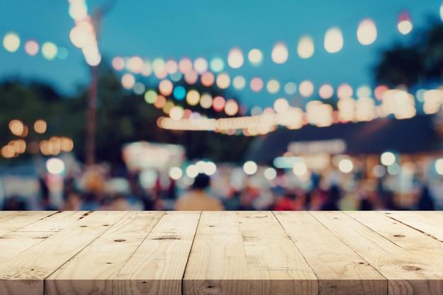 空の木製テーブルとナイトマーケットで背景をぼかした写真