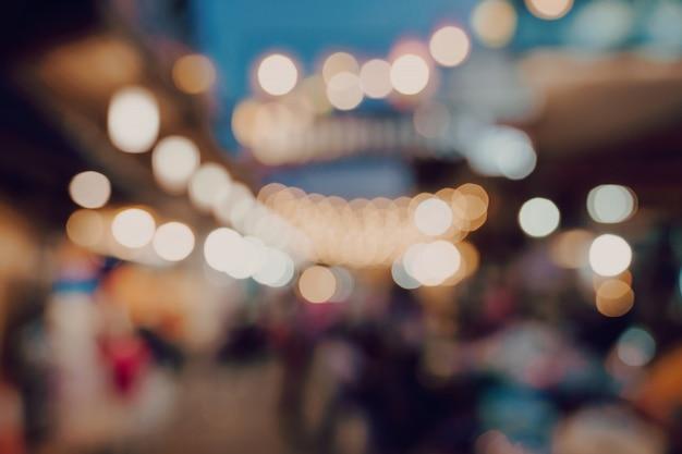 Размытым фон на ночной рынок фестиваль люди, идущие по дороге.