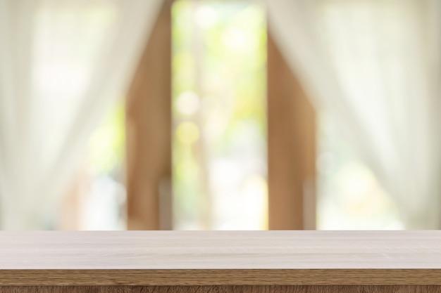 空の木製テーブルとコピースペースを持つウィンドウの背景をぼかし、製品のモンタージュを表示します。