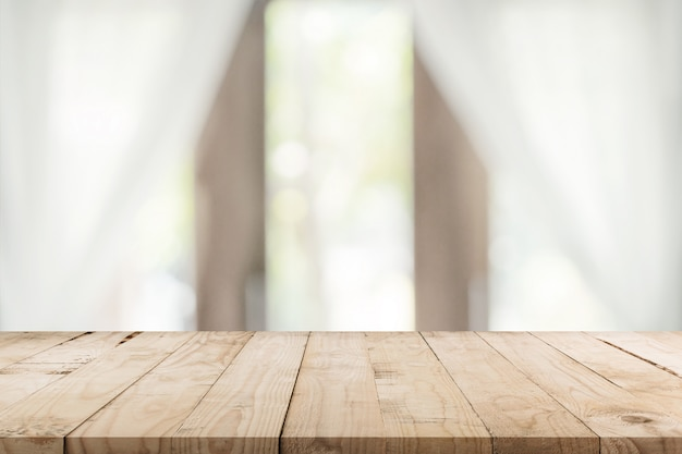 Опорожните деревянный стол и запачкайте предпосылку окна с космосом экземпляра, монтажом дисплея для продукта.