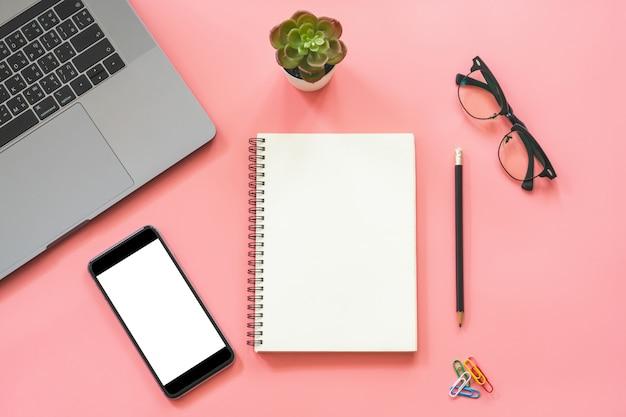 ノートパソコン、空白のノートブック、スマートフォン、鉛筆、文房具とワークスペースデスクの脂肪レイアウトデザイン