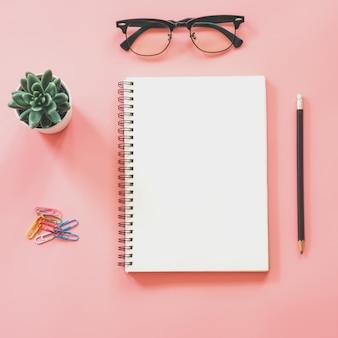 空白のノートブック、スマートフォン、コーヒー、コピースペースを持つ文房具とワークスペースデスクのフラットレイアウトモックアップデザイン