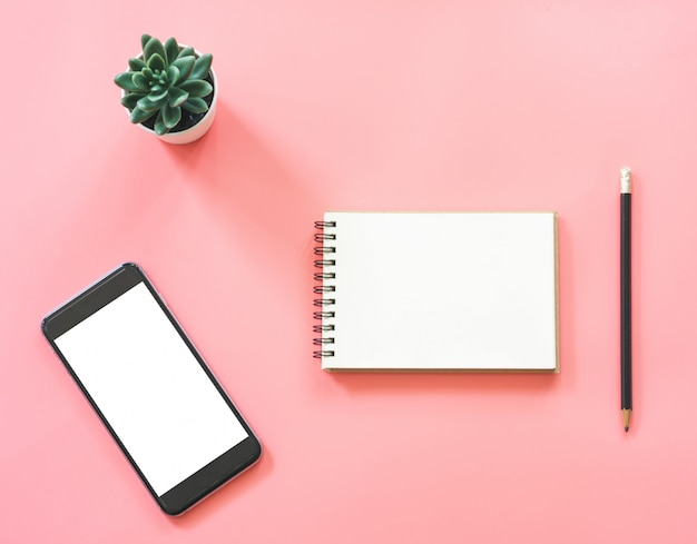 空白のノートブック、スマートフォン、コーヒー、コピースペースとピンクのパステルカラーのひな形付きワークスペースデスクのフラットレイアウトモックアップデザイン