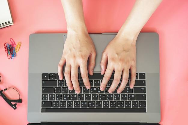 アクセサリーとピンクのパステル調のカラフルなオフィスでラップトップに入力する女性