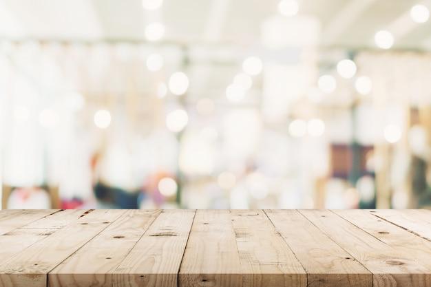 空の木製テーブルと背景をぼかした写真 - ショッピングモールの店は、製品の表示モンタージュと背景のボケ味をぼかし。