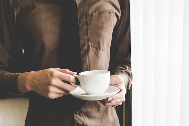 ウィンドウでコーヒーカップを保持している実業家。創造的なビジネスのスタートアップのアイデア。