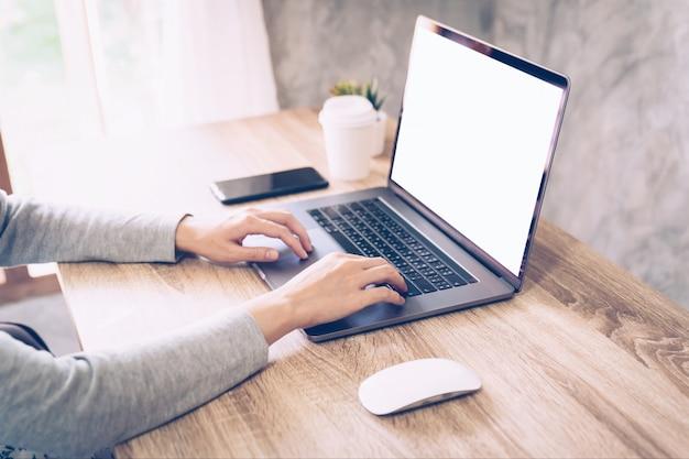 木製のテーブルで作業するためのコンピューターのラップトップを使用してアジアの女性