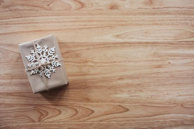 木製の背景に茶色のギフトとクリスマスの装飾の上