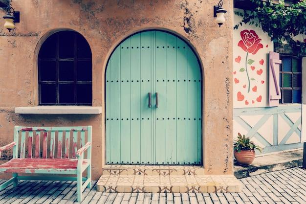 古いドアと家の木製の椅子の前