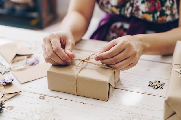 クリスマスの装飾が施された木製のテーブルにラッピングギフトボックスを保持している手のクローズアップ。