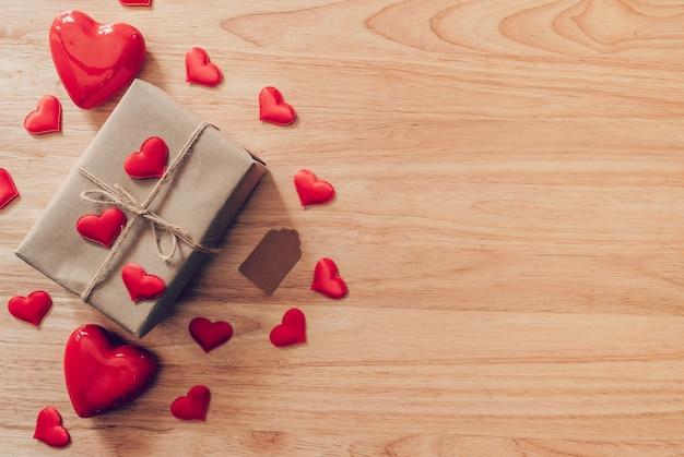コピースペースとバレンタインデーの木製の背景に平面図茶色ギフトボックスと赤いハート。