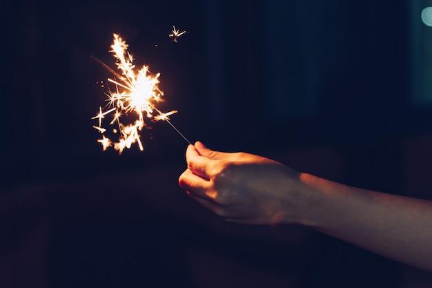 Крупным планом рука женщина, держащая бенгальские огни в ночной вечеринке