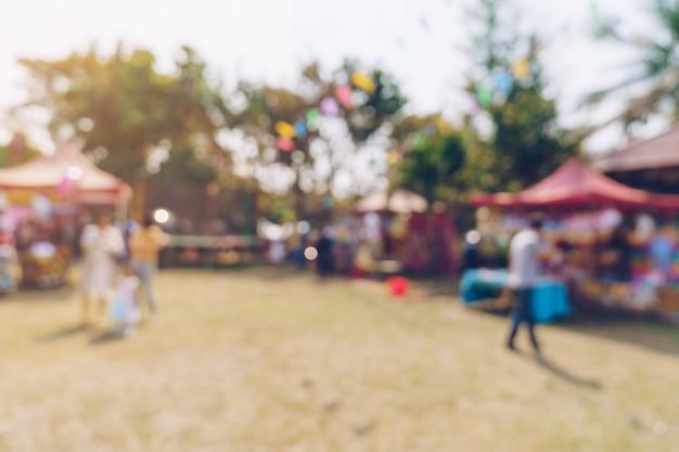 抽象的なぼかしの人々と背景のボケ味を持つ都市公園の庭のお祭りで日光。