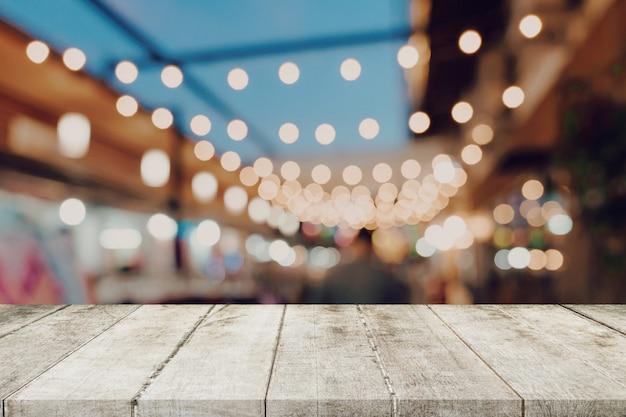 コピースペースが付いている道の上を歩くナイトマーケットフェスティバルの人々で空の木製テーブルは、製品のモンタージュを表示します。