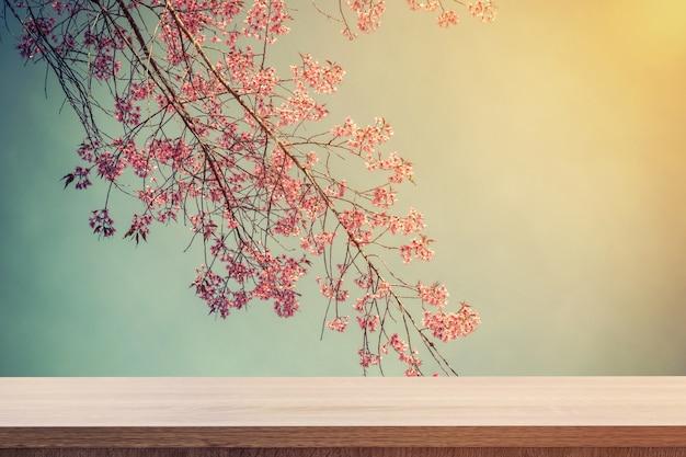 製品の配置やモンタージュ、ヴィンテージ調のピンクの花のための空の木製テーブル。