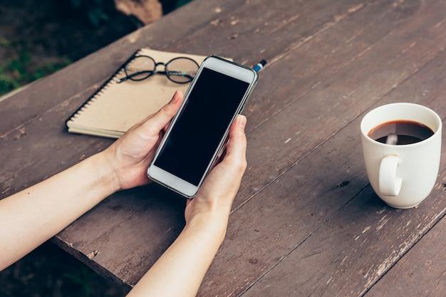 あなたの広告のための空白のコピースペース画面で電話を持っている女性の手。コーヒーショップで電話を使用して手の女性。
