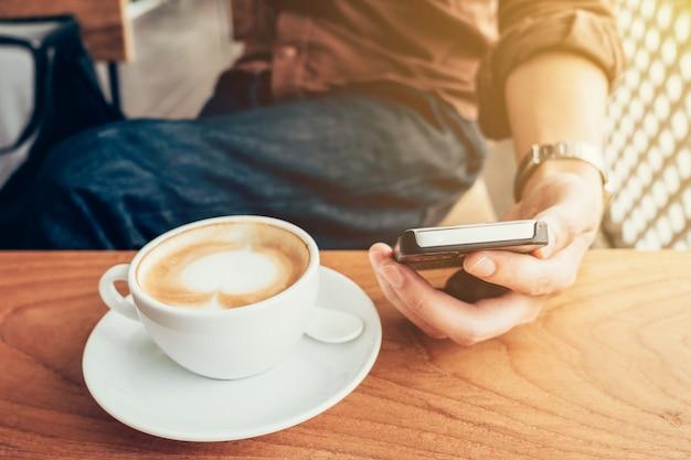 ビンテージフィルターとコーヒーショップで電話を使用して手男。