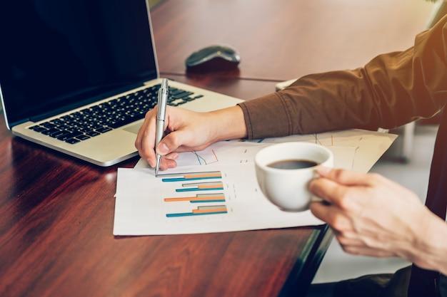 オフィスで木製のテーブルに紙のシートを書くビジネスマン。