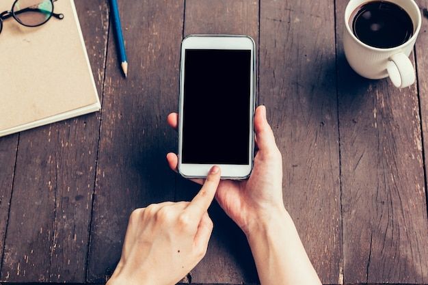 あなたの広告のための空白のコピースペース画面で電話を持っている女性の手を閉じます。コーヒーショップで電話を使用して手の女性。