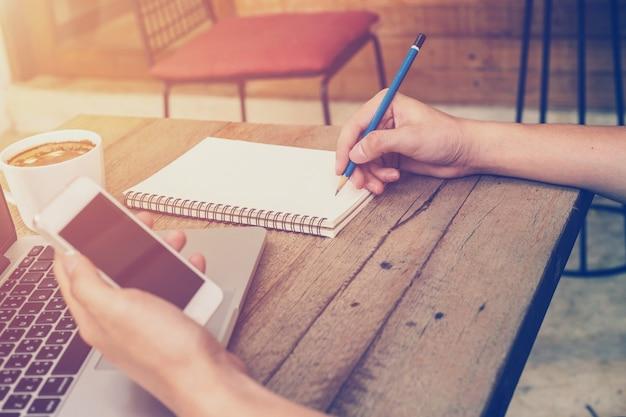 若い、ビジネスマン、電話、書類、ビンテージフィルター付きのコーヒーショップでラップトップを使用して手。