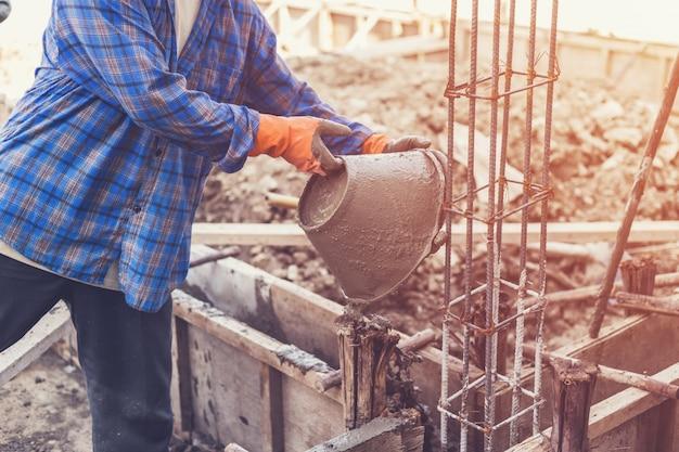 Человек рабочий смешивания цементного раствора штукатурки для строительства с старинным тоном.
