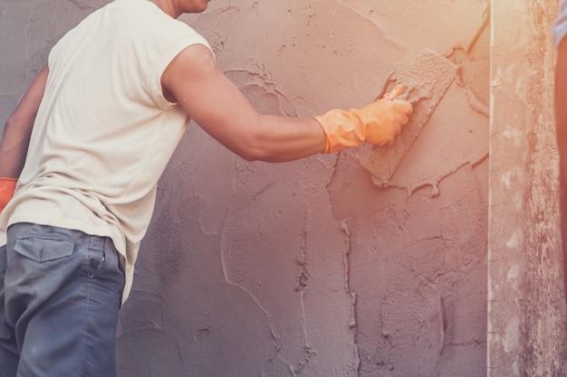 Человек штукатурный бетон на цемент для стены в строительстве здания с винтажным тоном.