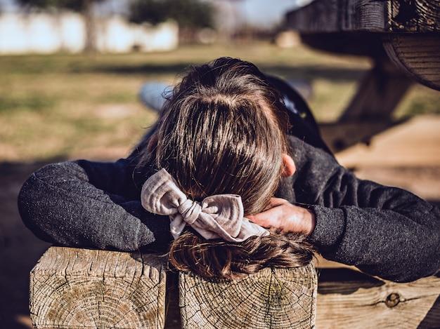 Девушка лежала на открытом воздухе на деревянной скамейке