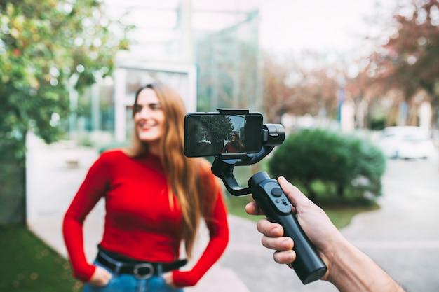 赤、ライフスタイルコンセプトに身を包んだ路上で女の子を携帯電話で記録