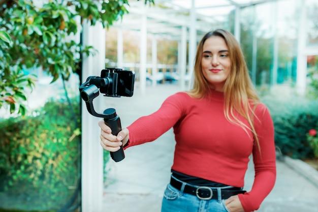 彼女の携帯電話、ライフスタイルコンセプトで自分自身をビデオ撮影、赤い服を着て大人の女の子