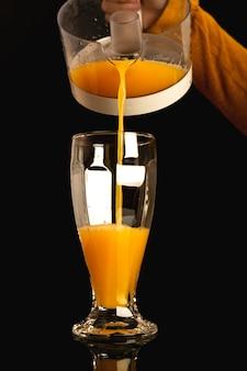 黒の背景、健康概念のガラスにオレンジジュースを注ぐ