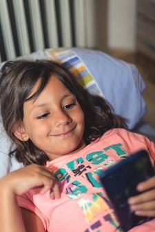 幸せな携帯電話、ライフスタイルコンセプトを遊んでベッドに横たわっている少女