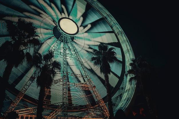Колесо обозрения, снятое ночью с длинной выдержкой, чтобы запечатлеть круговые движения огней. на черном фоне