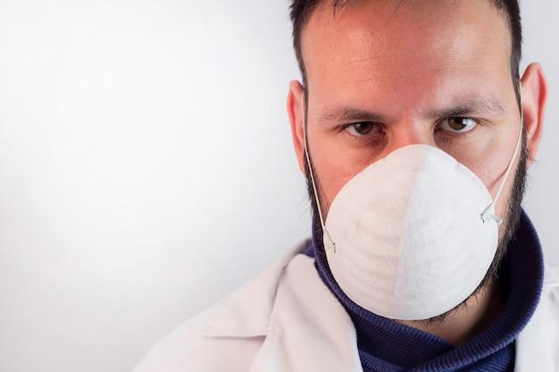 白い背景の上のマスクを持つ医師の肖像画