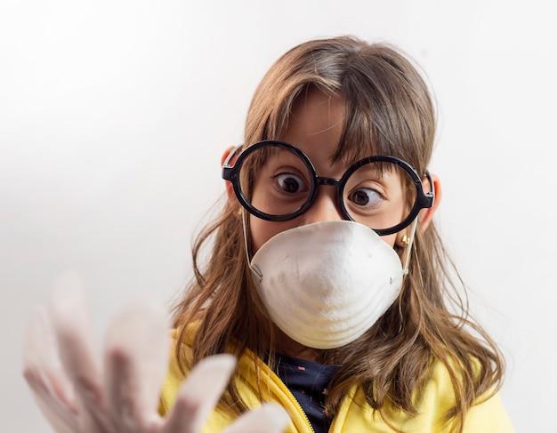ラテックス手袋を身に着けているマスクの少女