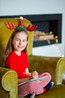 サンタ帽子をかぶったかわいい女の子が、クリスマスツリーの近くでサンタに手紙を書きます。幸せな子供時代、欲望を満たすための時間。