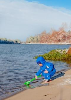 Маленький мальчик копать и играть в зимний снег, дети зимние мероприятия.