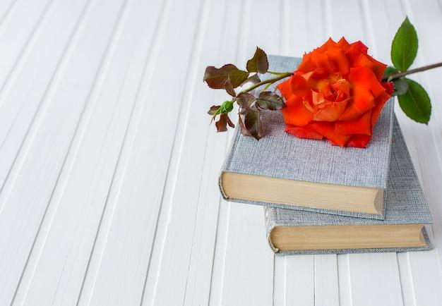 白い木製の背景、ロマンチックな愛の開いた本の上の赤いバラの花。
