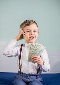 Милый мальчик, играя с большим количеством денег, как говорить по телефону, американские сто долларов наличными. американец сто долларов наличными.