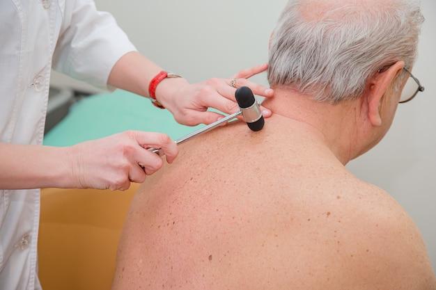 Хирург-ортопед осматривает коленный рефлекс. врач проверяет физиологический рефлекс, тест молотка.