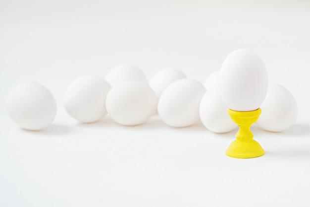 木製のコースターに白い卵は白い背景を形成します。イースター休暇の準備をします。