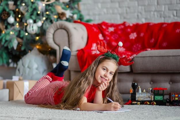 サンタの帽子をかぶったかわいい女の子が、クリスマスツリーの近くでサンタに手紙を書きます。幸せな子供時代、欲望を満たすための時間。