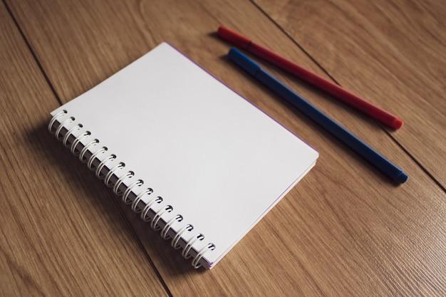 Блокнот для письма и разноцветные ручки на столе